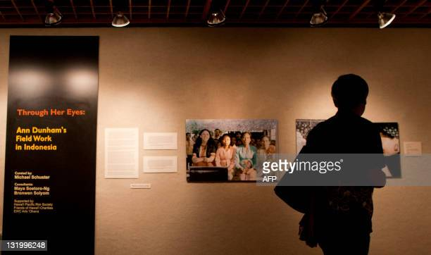 A visitor looks at photographs taken during fieldwork in Indonesia by S Ann Dunham US President Barack Obama's late mother during an exhibition at a...
