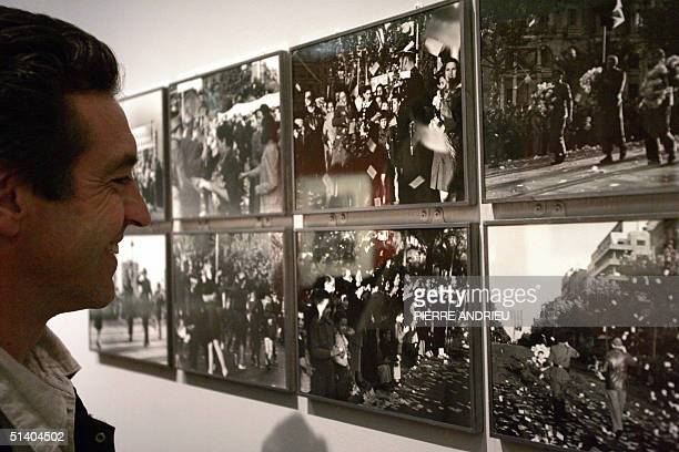 A visitor looks at photojournalist Robert Capa's photos who died fify years ago 05 October 2004 at Bibliotheque nationale de France in Paris during...
