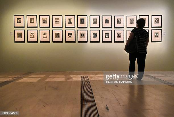 A visitor looks at pictures at the art exhibition 'Journey to Infinity Escher's World of Wonder' which showcases the works of world famous graphic...