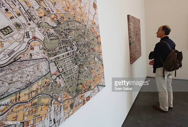 A visitor looks at pieces made from city maps in the installation 'Das Gift' by artist Yoko Ono at the Haunch of Venison gallery on September 10 2010...