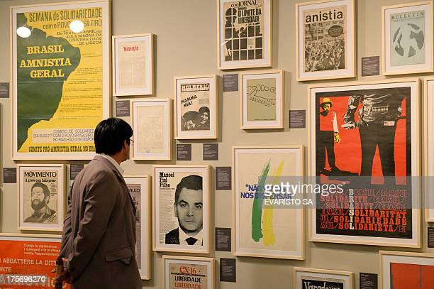A visitor looks at posters at 'Resisting is Necessary' considered as Brazil's largest exhibition of art and journalism resistance against the...
