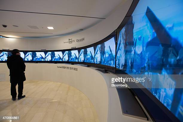 A visitor looks at Samsung Electronics Co curved Ultra High Definition televisions displayed at a media event in Seoul South Korea on Thursday Feb 20...