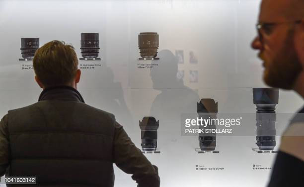A visitor looks at Sigma lenses at the Sigma stand at the Photokina trade fair in Cologne western Germany on September 27 2018 The fair for the...