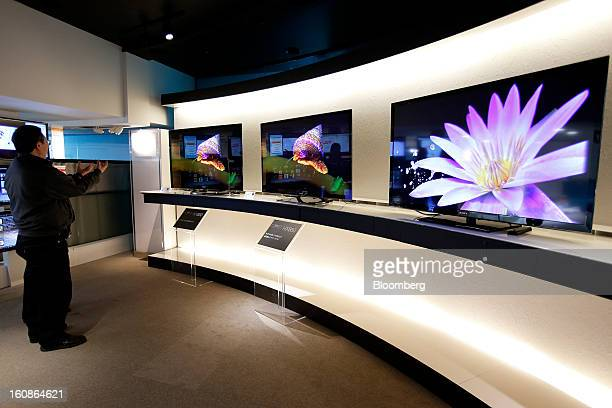 A visitor looks at Sony Corp's Bravia televisions displayed at the company's showroom in Tokyo Japan on Thursday Feb 7 2013 Sony Japan's biggest...
