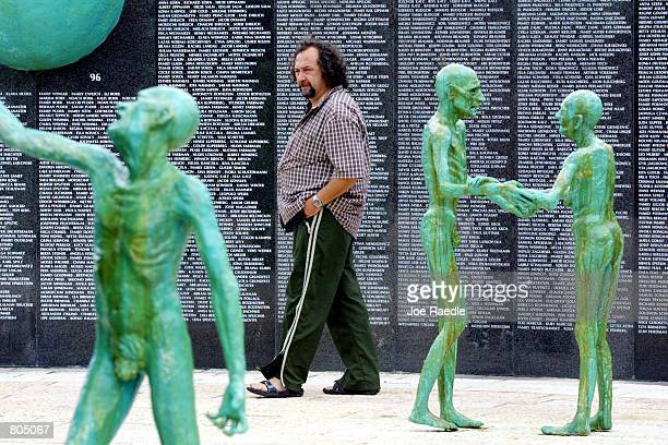A visitor looks at statues by artist Kenneth Treister which are on display as part of a memorial depicting thousands of victims crawling into an open...