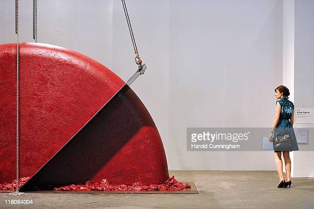 A visitor looks at the Anish Kapoor Push Pull 2008 artwork on June 14 2011 in Basel Switzerland 300 art galleries selected by the fair will display...