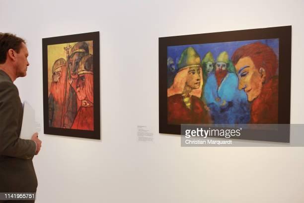 """Visitor looks at the art work 'Nordic People' during the preview of the exhibition """"Emil Nolde - Eine deutsche Legende. Der Kuenstler im..."""