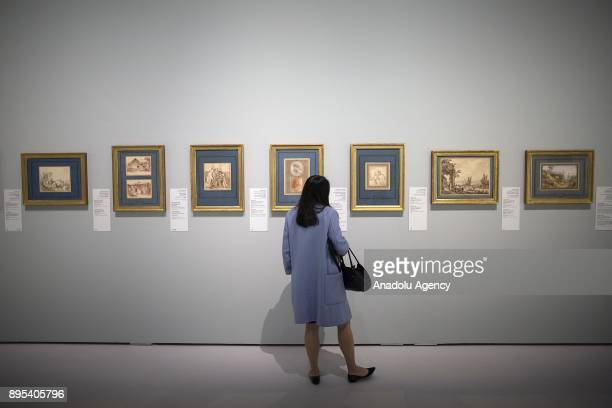 A visitor looks at the arts during the press preview of the 'From One Louvre to Another' exhibition at the Louvre Abu Dhabi in Abu Dhabi United Arab...