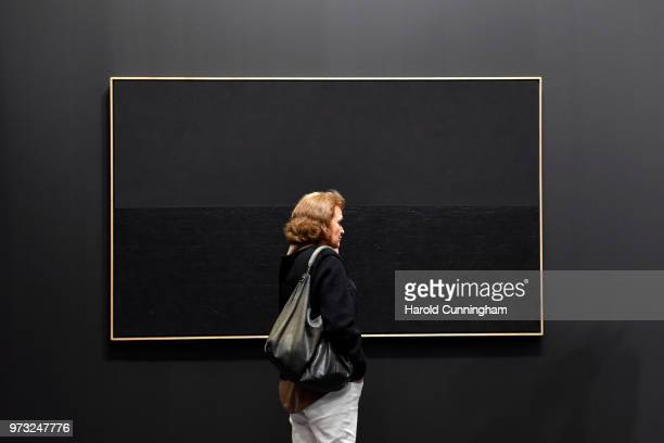 A visitor looks at the artwork of Alberto Burri 'Nero Collotex' during the press preview for Art Basel at Basel Messe on June 13 2018 in Basel...