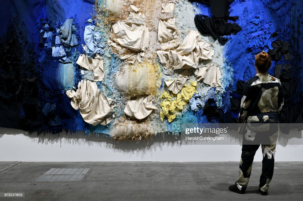 A visitor looks at the artwork of Josep Grau-Garriga 'Hores de llum i de foscor' during the press preview for Art Basel at Basel Messe on June 13, 2018 in Basel, Switzerland. Art Basel is one of the most prestigious art fair in the world showcasing the work of more than 4,000 artists selected by 300 leading art galleries.