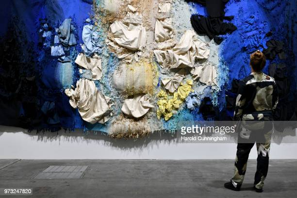 A visitor looks at the artwork of Josep GrauGarriga 'Hores de llum i de foscor' during the press preview for Art Basel at Basel Messe on June 13 2018...