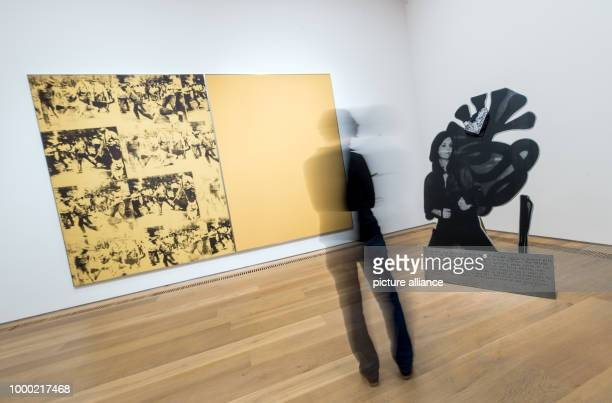 A visitor looks at the artworks Mustard Race Riot and Tanya as a Bandit  from Andy Warhol shown in the exhibition Pop Pictures People in Munich...