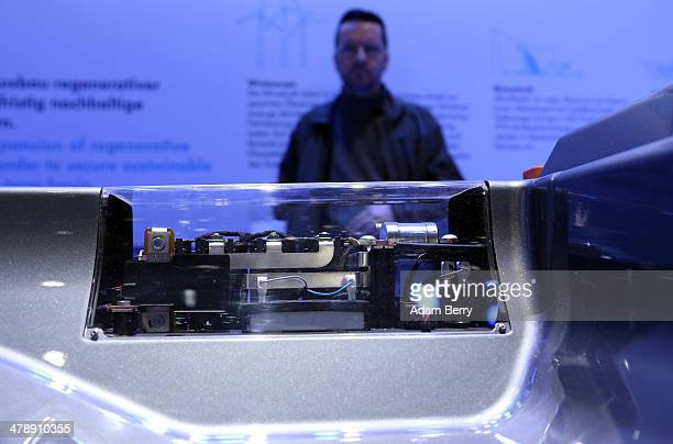 Visitor looks at the battery of a Volkswagen e-Up! electric automobile at the Electric Mobility Week , a public Volkswagen event at the former...