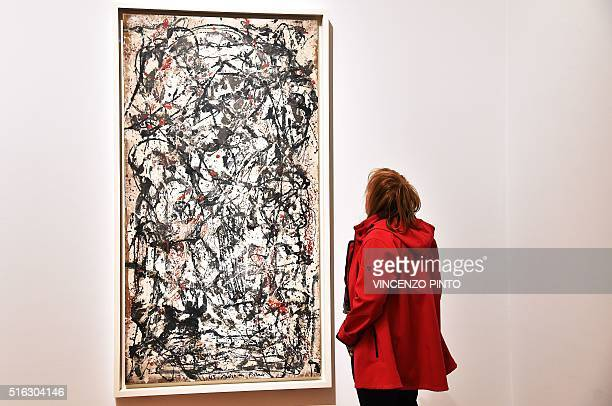 A visitor looks at the 'Enchanted forest' by US painter Jackson Pollock during a press preview of the exhibition 'From Kandinsky to Pollock the art...