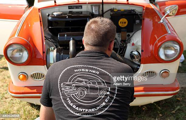 A visitor looks at the engine of a 1963 Trabant P60 automobile at a Trabant enthusiasts' weekend on August 8 2015 near Nossen Germany The Trabant...