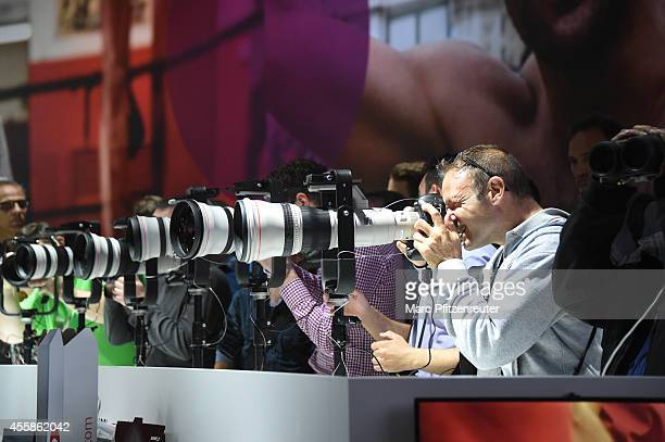 Visitor looks at the latest Canon digital cameras at the 2014 Photokina trade fair on September 21 2014 in Cologne Germany Photokina is the world's...