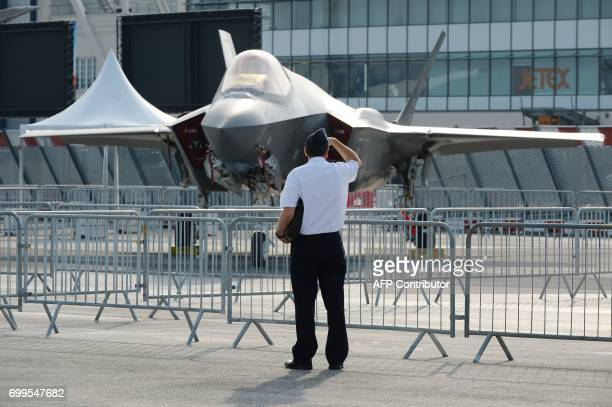 A visitor looks at the Lockheed Martin F35 jetfighte on the tarmac at Le Bourget on June 22 2017 during the International Paris Air Show / AFP PHOTO...