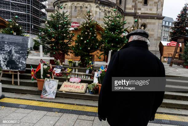 A visitor looks at the memorial for the victims of the terrorist attack on the Christmas market in 2016 as the Christmas market on Breitscheidplatz...