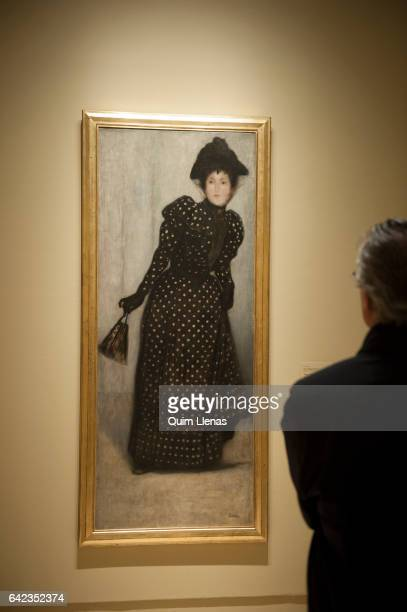 A visitor looks at the paint 'Mujer con vestido de lunares blancos' by Jozsef RippiRonai during the press preview of the exhibition 'Obras maestras...