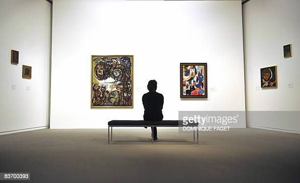 A visitor looks at the painting Disobedience masks by Constant and The Detested Town by Asger Jorn on November 13 2008 during the exhibition Cobra at...