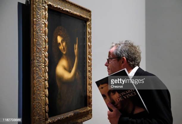 Visitor looks at the painting entitled 'Saint Jean Baptiste' by the Italian Renaissance artist, Leonardo da Vinci, during a press visit of the...