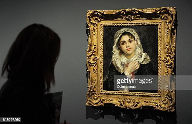 A visitor looks at the painting 'Lise con un chal blanco' by french painter Renoir during the press opening of the exhibition 'Renoir Intimidad' at...