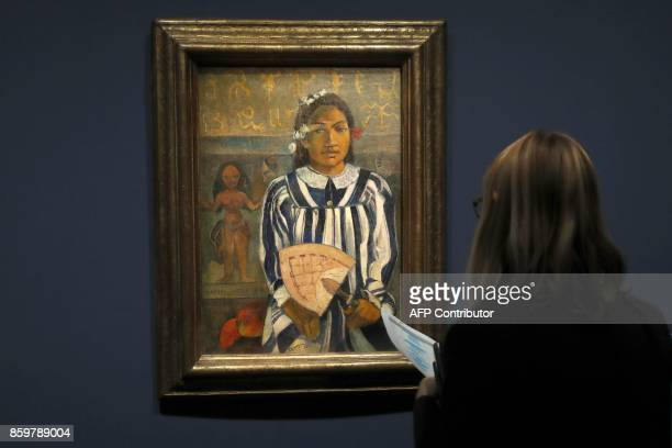 A visitor looks at the painting 'Merahi metua no Tehamana' by French painter Paul Gauguin during the exhibition entitled 'Gauguin the alchimist' at...
