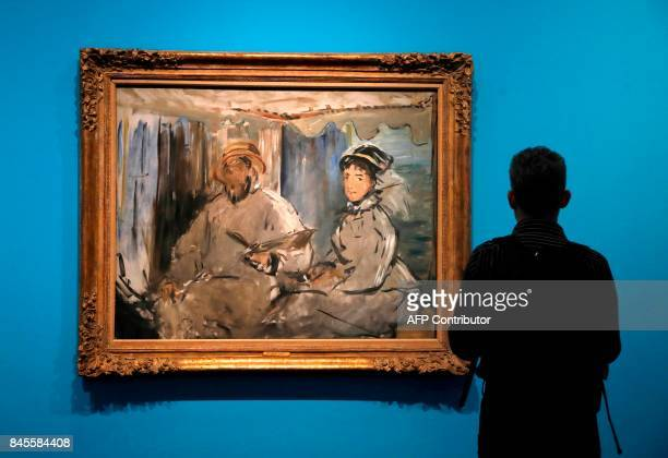 A visitor looks at the painting 'Monet peignant dans son atelier ' by French painter Edouard Manet during a press visit of the exhibition 'Monet...