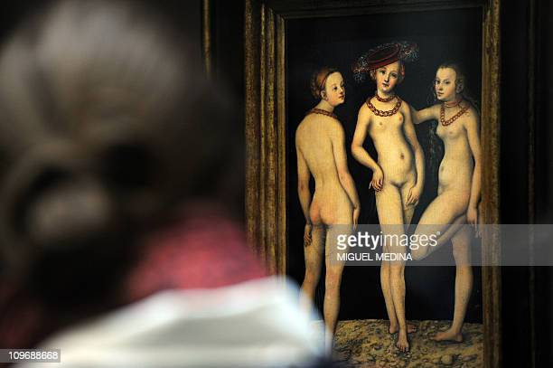 A visitor looks at the painting of German Renaissance master Lucas Cranach Les Trois Graces known as a masterpiece of the Renaissance period during...
