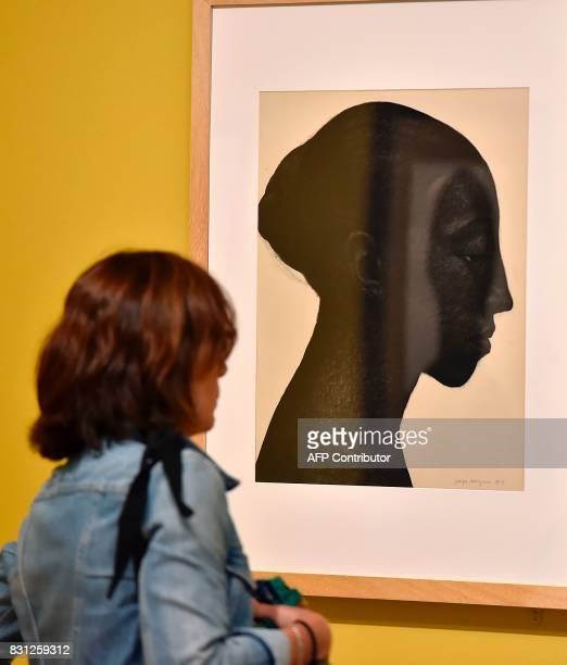 A visitor looks at the painting 'Portrait de femme au chignon' by French artist and painter Georges Dorignac during the exhibition 'Georges Dorignac...