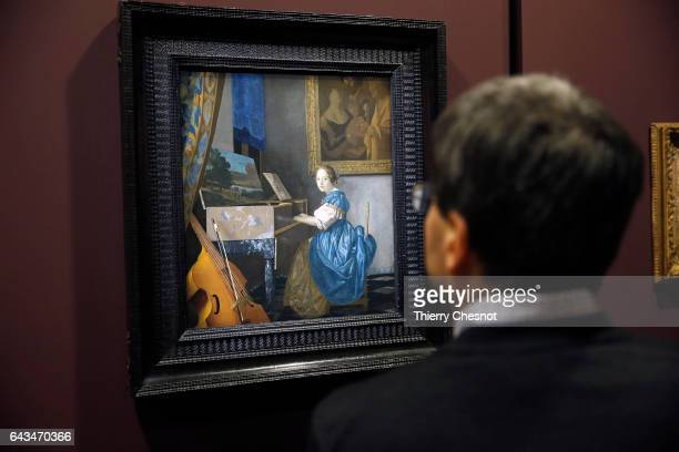 A visitor looks at the painting 'The Milkmaid' by Dutch painter Johannes Vermeer during a press visit of the exhibition 'Vermeer and the Masters of...
