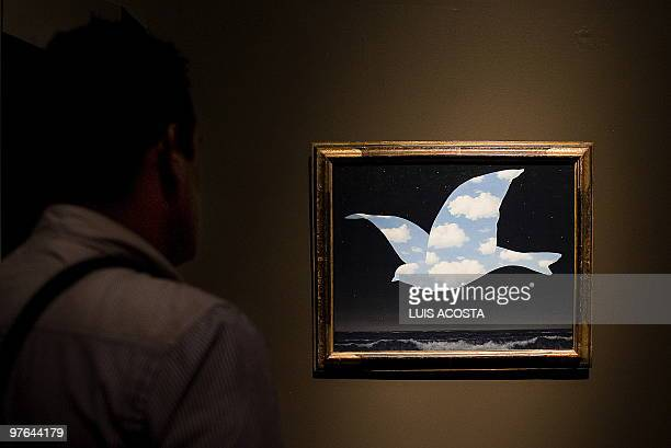 A visitor looks at the painting The Promise by Belgian artist Rene Magritte exhibited during a press conference at the Fine Arts Palace in Mexico...