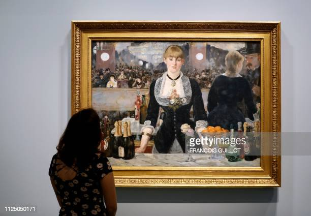 A visitor looks at the painting Un Bar aux FoliesBergere by French painter Edouard Manet during the press visit of the exhibition The Courtauld...