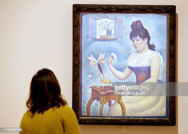 A visitor looks at the painting Young Woman Powdering Herself by French painter Georges Seurat during the press visit of the exhibition The Courtauld...