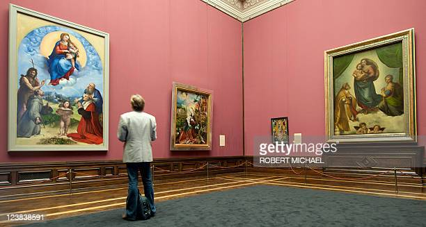 A visitor looks at the paintings 'Sixtinische Madonna' and the 'Madonna di Foligno' wich are closely related by Italian artist Raphael and displayed...