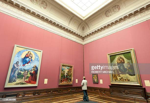 A visitor looks at the paintings 'Sixtinische Madonna' and the 'Madonna di Foligno' wich are closely related by Italian artist Raphael displayed at...