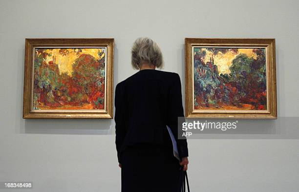 A visitor looks at the paintings 'The house seen from the rose garden' during the preview of the Melbourne Winter Masterpiece exhibition 'Monet's...