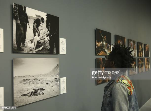 A visitor looks at the photos of Danish Photo Journalist Jan Grarup winner of the Second Prize in the News Story category with his The Battle for...