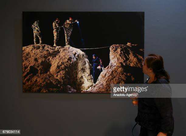 A visitor looks at the photos of French Photo Journalist Frederic Lafargue who works for Paris Match winner of the 'Photo of the Year 2016' in the...