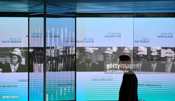 Visitor looks at the portraits of the Israeli athletes murdered at the 1972 Munich Olympics at the Olympic Village displayed inside the Memorial...