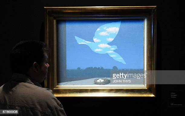 A visitor looks at 'The Returns 1940 ' a painting by the Belgian artiste Rene Magritte displayed at the press opening of the new Magritte museum in...