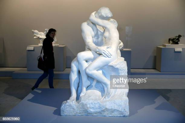 A visitor looks at the sculpture 'The Kiss 18811882' by French sculptor Auguste Rodin during the press preview 'Rodin the centennial exhibition' at...