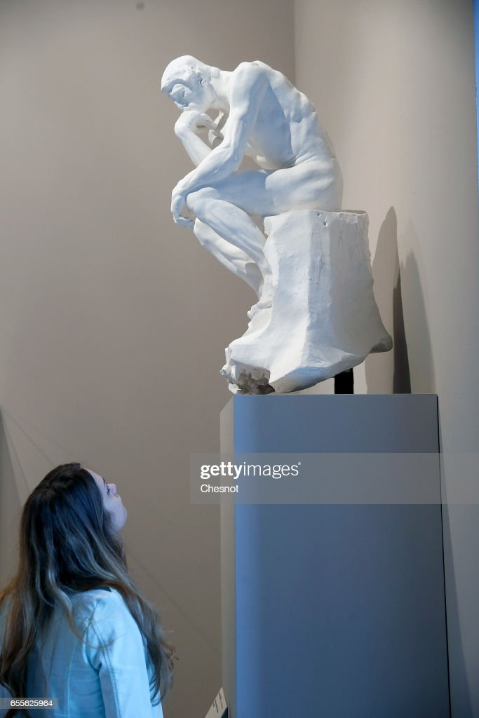 A visitor looks at the sculpture ' The Thinker, on marquee element, 1881-1888' by French sculptor Auguste Rodin (1840-1917) during the press preview 'Rodin the centennial exhibition' at the Grand-Palais on March 20, 2017 in Paris, France. To mark the centenary of his death, the Rodin museum and the Grand-Palais are joining forces to celebrate Auguste Rodin (1840-1917). This exhibition takes part from March 22 to July 31, 2017.