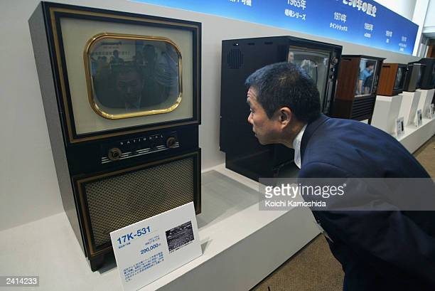 A visitor looks at the very first television ever released by the Matsushita Electric Industrial Co Ltd August 21 2003 in Tokyo Panasonic introduced...
