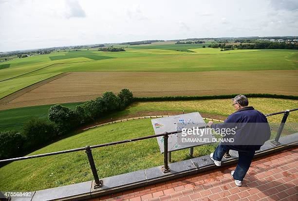 A visitor looks at the view from atop La Butte du Lion the main memorial monument of the Battle of Waterloo in front on a field where the 1815 Battle...