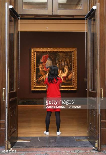 A visitor looks at Titian's 'Diana and Actaeon' one of the most celebrated masterpieces of the Italian Renaissance at the National Gallery London