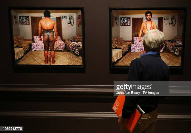 A visitor looks at two portraits by Mark Adams of Jim Taofinu'u during a press view for Oceania at the Royal Academy London which is the first major...