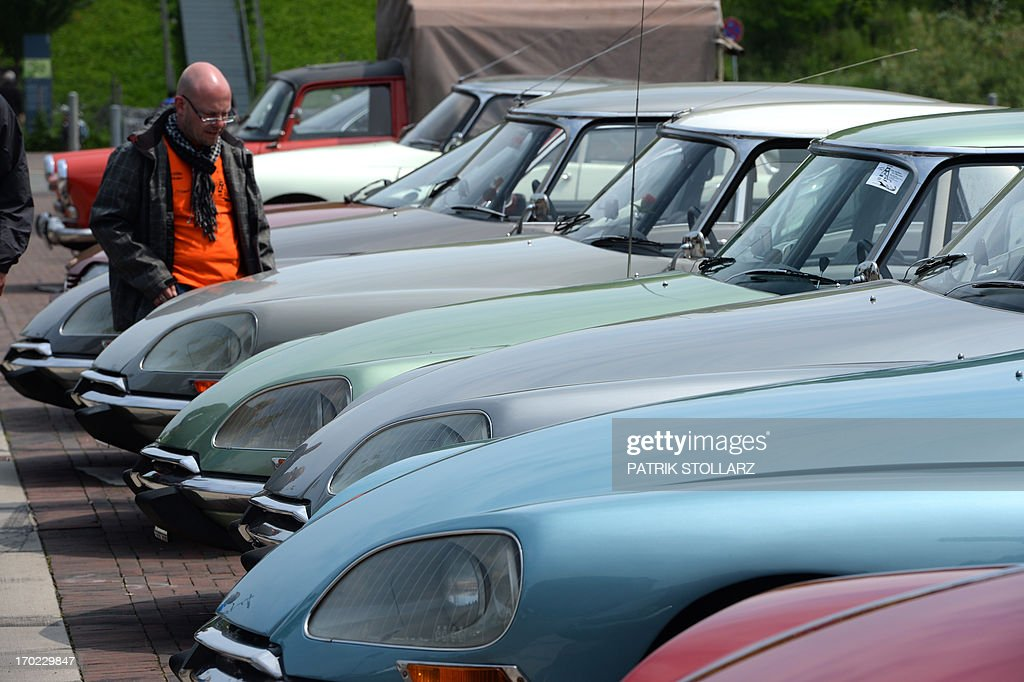 ac6f621342 A visitor looks at vintage Citroen DS cars parked in front of the ...