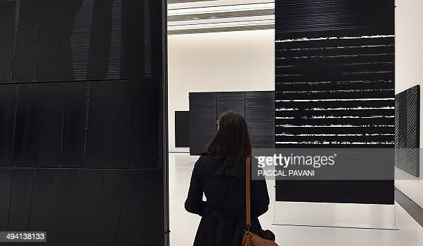 A visitor looks at works by French painter engraver and sculptor Pierre Soulages at the museum of the « Outrenoir » master on May 28 2014 in the...