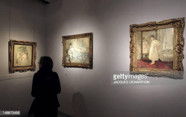 A visitor looks at works 'Sortant du lit' 'Jeune femme en gris étendue' and 'La psyché' during a retrospective dedicated to the French impressionist...